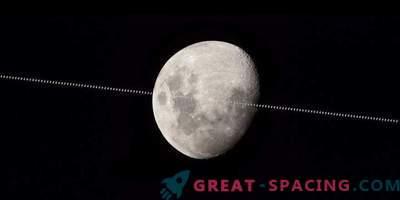 Die Internationale Raumstation fliegt vor dem Hintergrund des Mondes